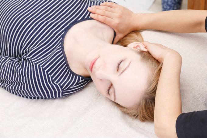 Une femme qui se fait soigner une céphalée cervicogénique.