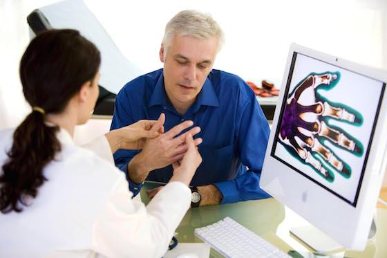 Un homme se faisant examiner pendant une séance de rhumatologie