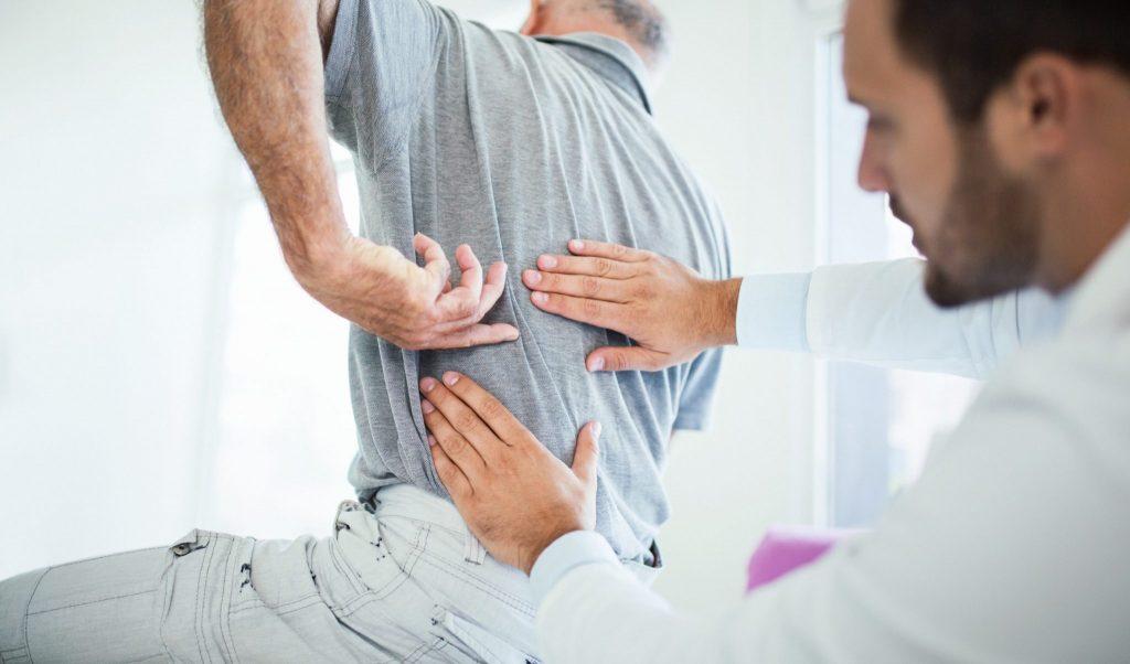 Un ostéopathe qui intervient sur un patient qui souffre de mal de dos