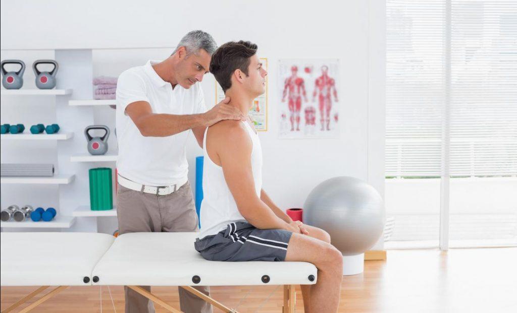 Un homme se faisant masser pendant une séance d'ostéopathie