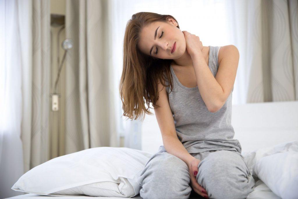 Une femme sur son lit ayant une douleur vive au coup de type cervicalgie en se levant le matin.